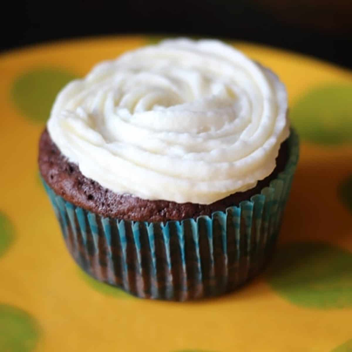 A chocolate cupcake topped with homemade buttercream frosting.