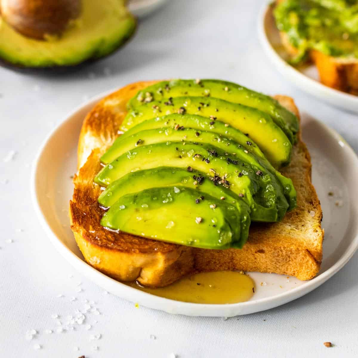 A slice of toast topped with thick slices of avocado, sea salt, course black pepper, and a drizzle of honey