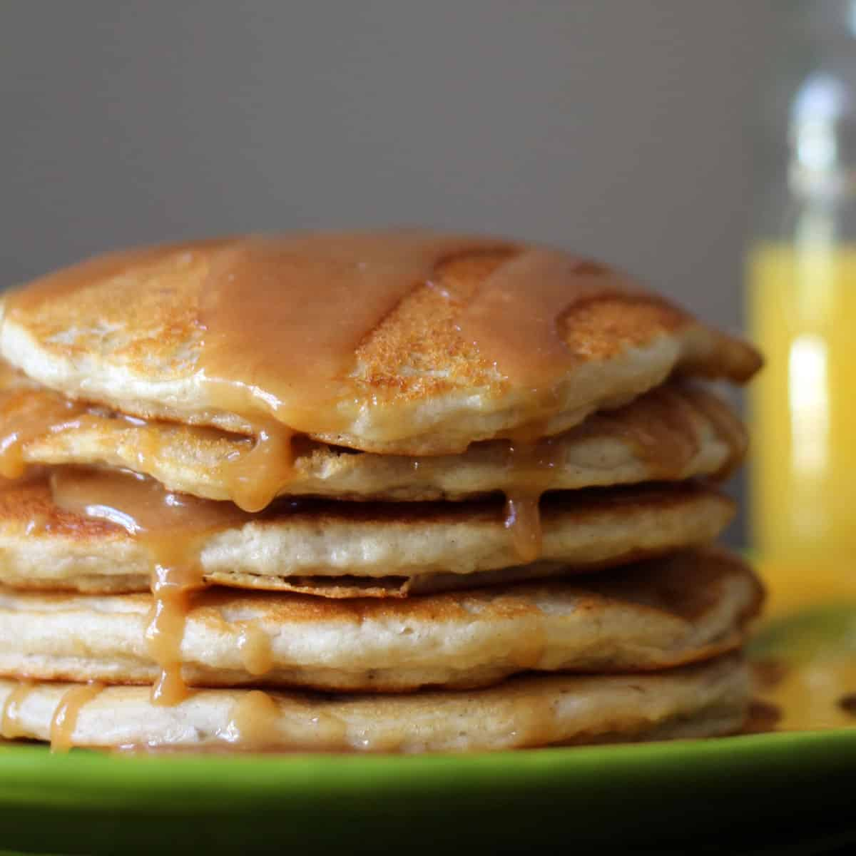 Stack of banana pancakes with syrup drizzled on top.