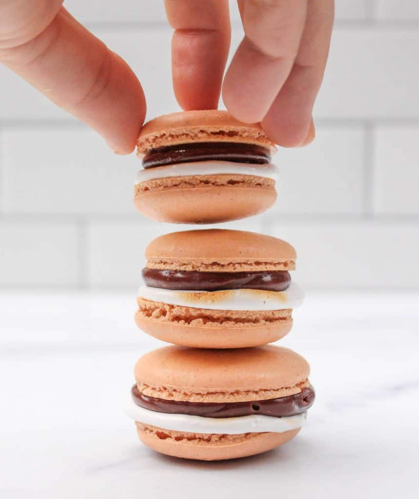 A hand stacking macarons.
