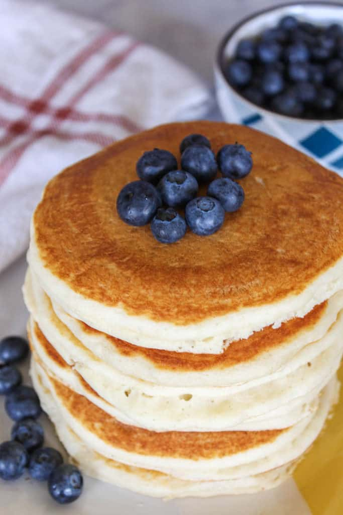 Stack of pancakes topped with fresh blueberries.