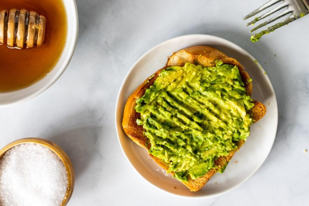 A slice of toast with mashed avocado on top and a fork off to the side