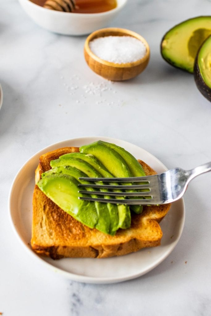 A fork sitting on top of thick slices of avocado on top of a piece of toast