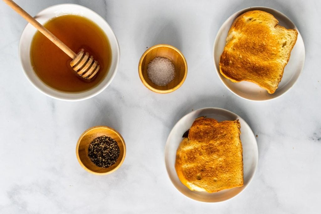 Ingredients on a counter including a bowl of honey, pinch bowls of sea salt and pepper and two slices of toast.