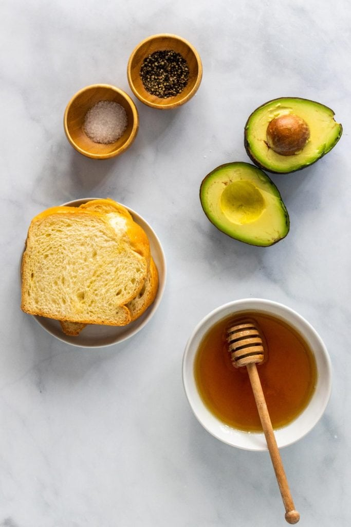 Ingredients spread out on the kitchen counter: avocado toast sliced in half, a bowl of honey, pinch bowls of salt and pepper, and two slices of bread.
