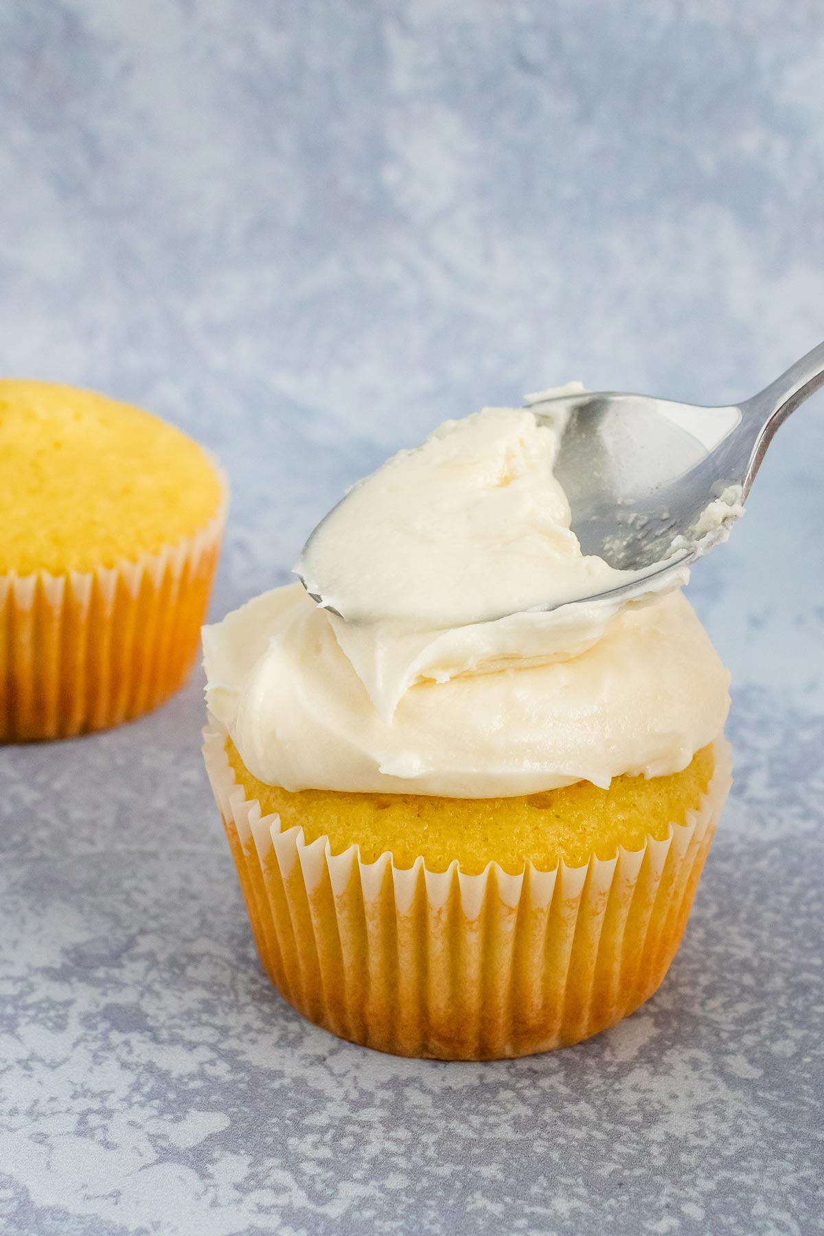 A vanilla cupcake being frosted with the back of a spoon.