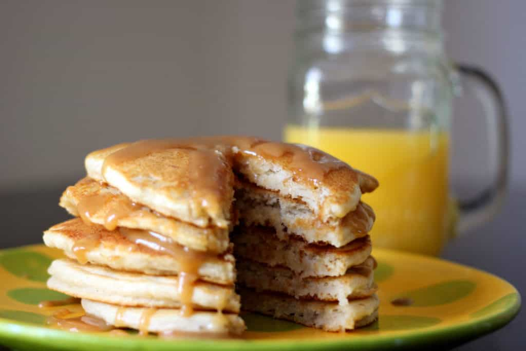 Stack of banana pancakes with a slice taken out.