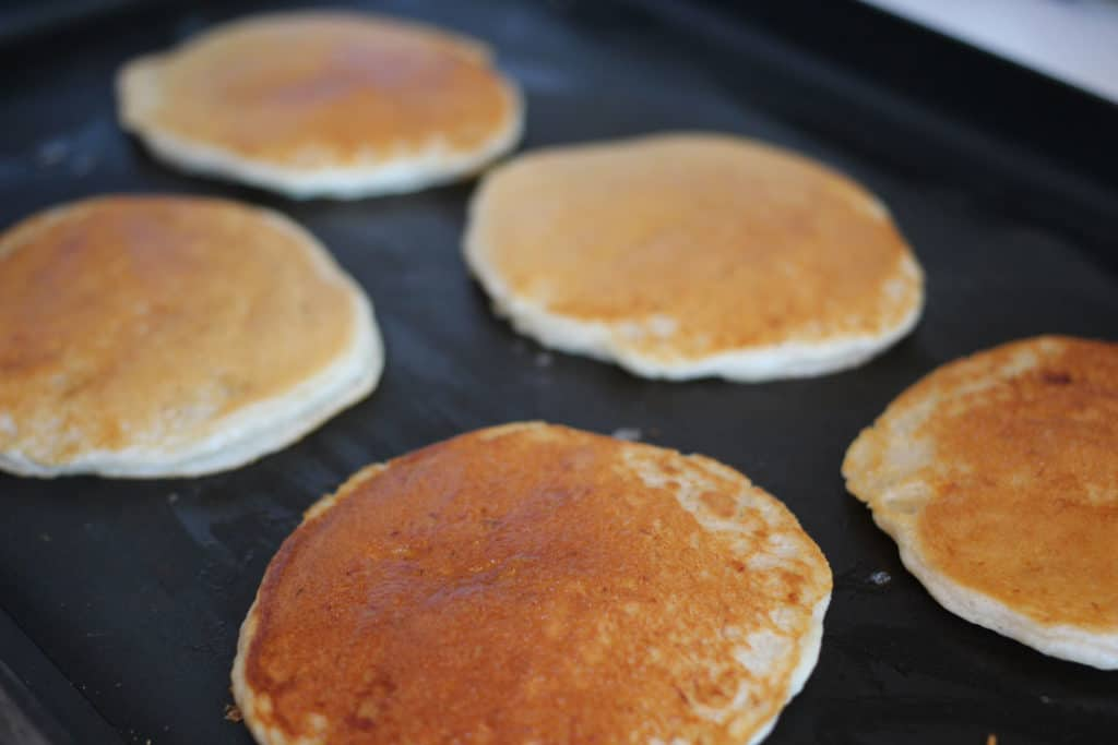 Pancakes cooking on the griddle.