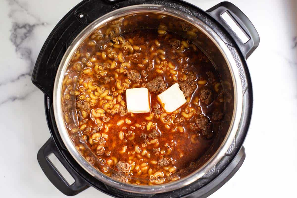 Ground beef, seasoning, and macaroni in beef broth, topped with butter in the Instant Pot.