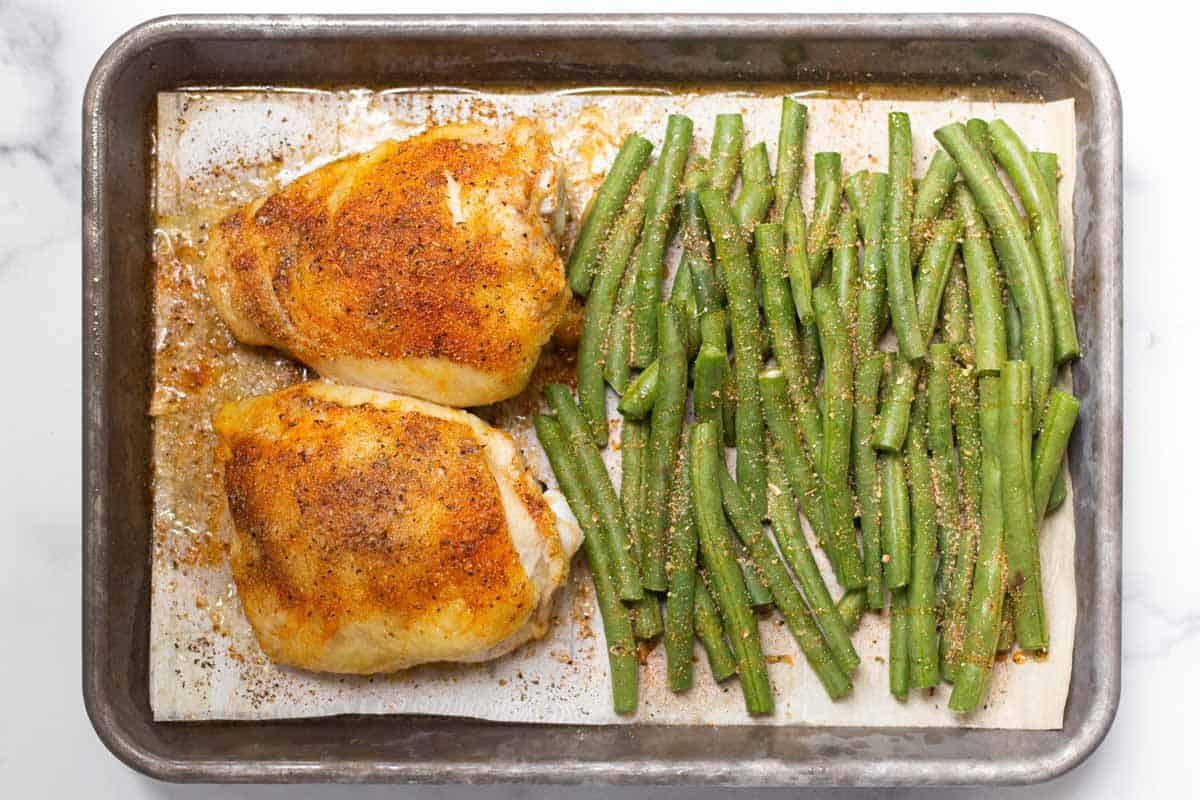 Partially cooked chicken thighs with uncooked and seasoned green beans with the ends trimmed.