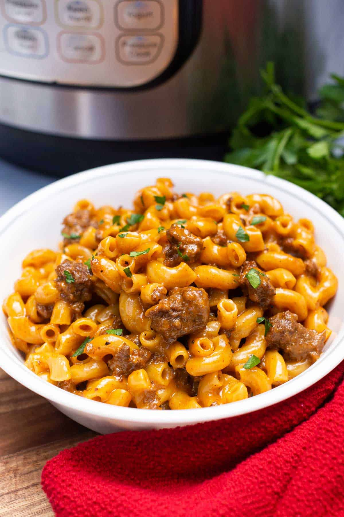 Bowl of Instant Pot Cheeseburger Macaroni garnished with fresh parsley.