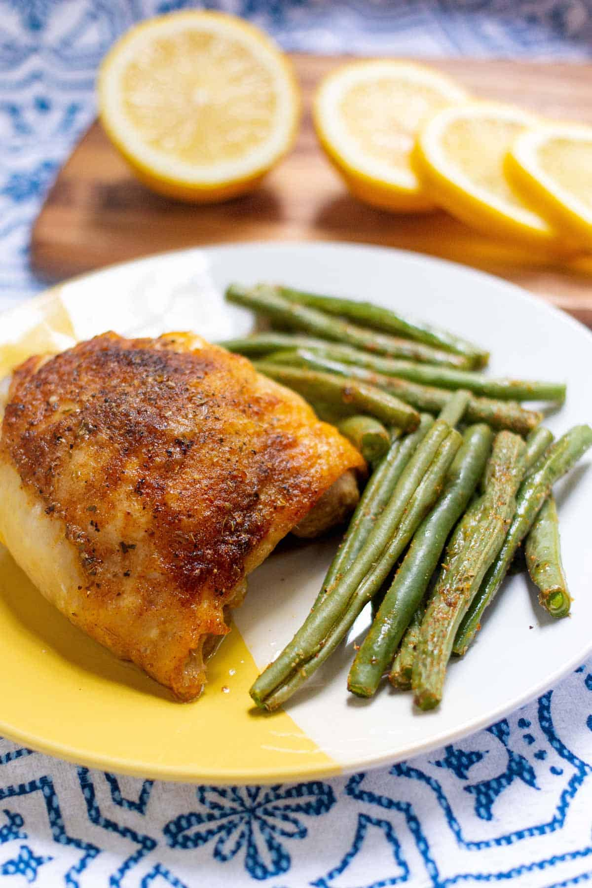 Baked chicken thigh plated with baked green beans.