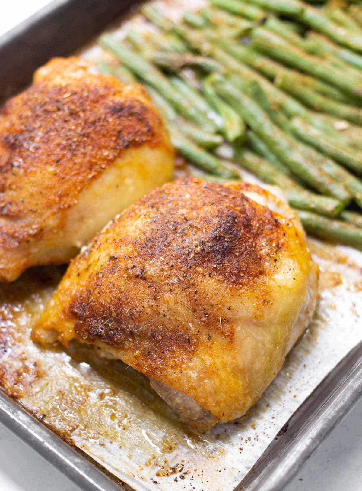 Close up of baked bone-in skin-on chicken thigh coated in seasoning with green beans in the background.