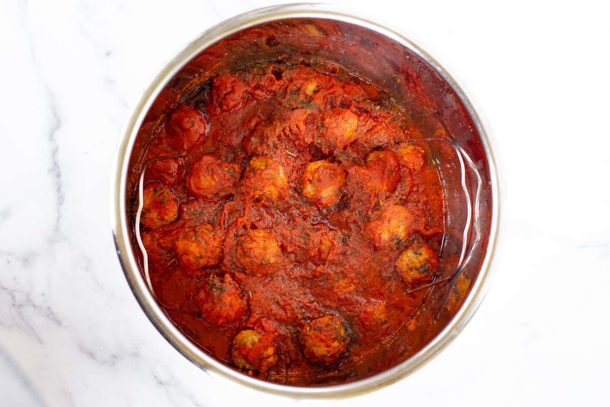 Cooked meatballs in pasta sauce in the pressure cooker.