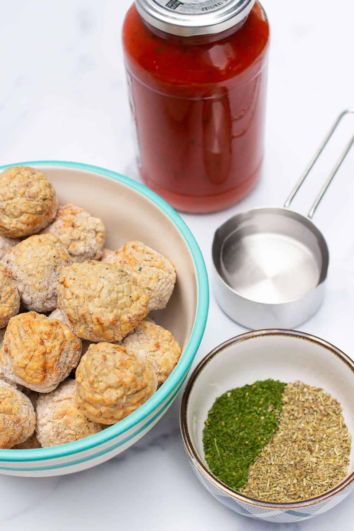 Instant Pot Italian Meatball Ingredients: water, frozen meatballs, pasta sauce, Italian seasoning, and parsley.