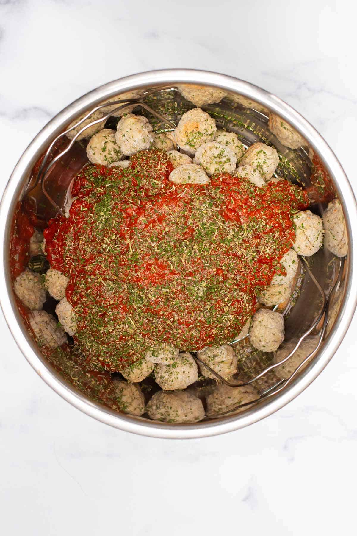Water, meatballs, pasta sauce, Italian seasoning, and parsley in the Instant Pot with a trivet at the base.