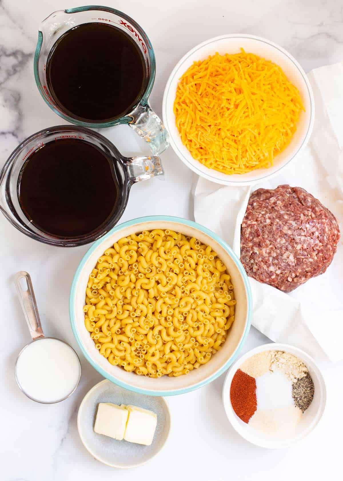 Instant Pot Cheeseburger Macaroni Ingredients: ground beef, elbow macaroni, beef broth, butter, paprika, onion powder, garlic powder, mustard powder, salt, ground black pepper, shredded cheddar cheese, and heavy whipping cream.