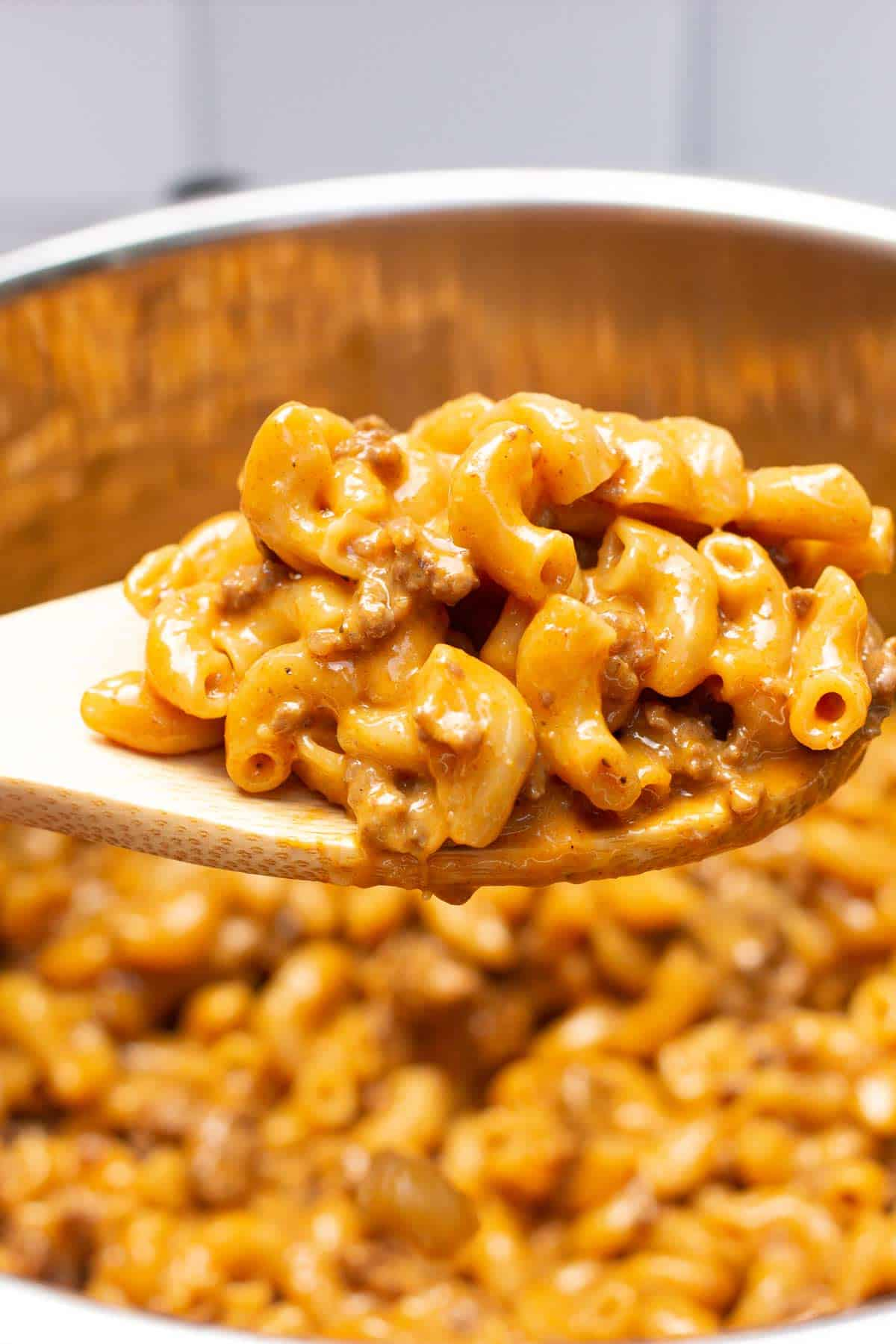 Instant Pot Cheeseburger Macaroni on a wooden spoon.