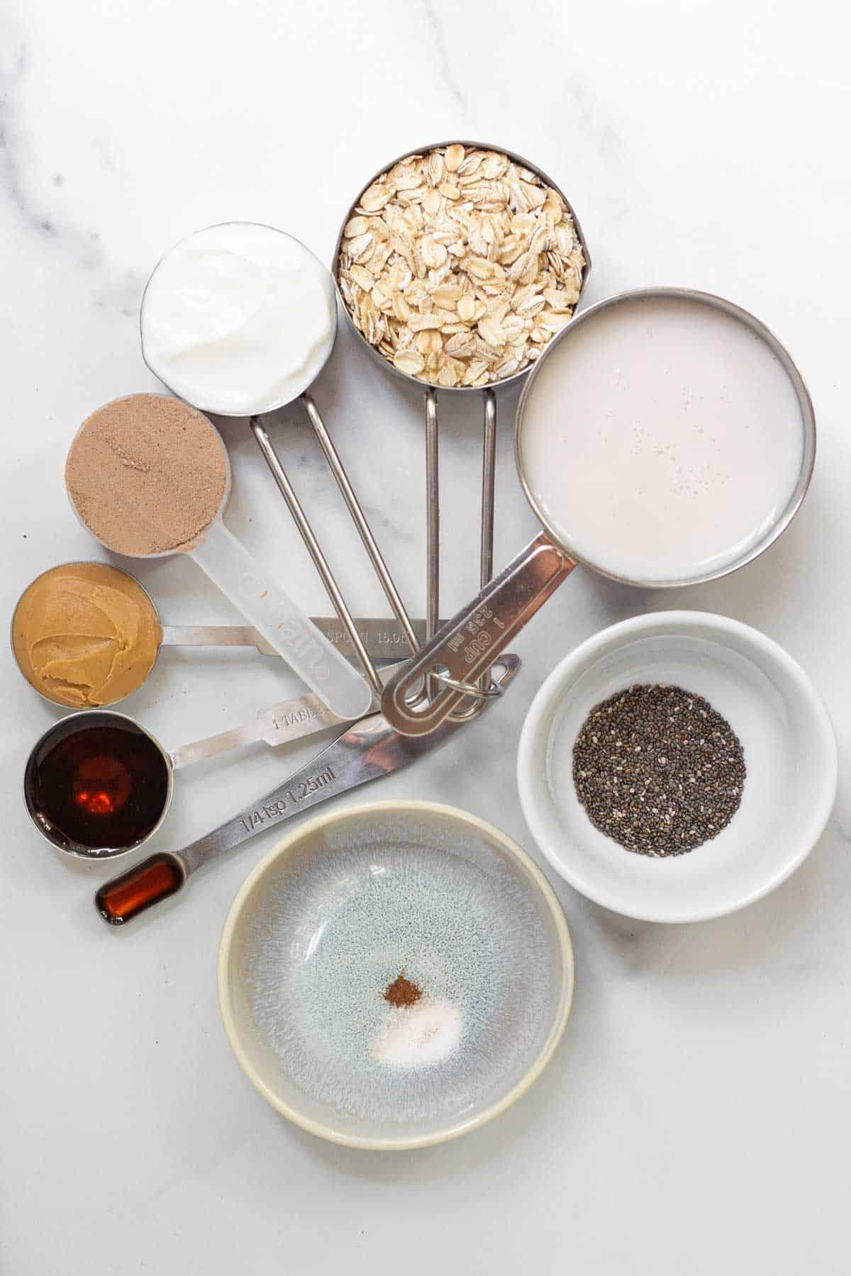 Protein Powder Overnight Oats ingredients: oatmeal, chocolate protein powder, almond milk, Greek yogurt, creamy peanut butter, maple syrup, chia seeds, vanilla extract, salt, and cinnamon.