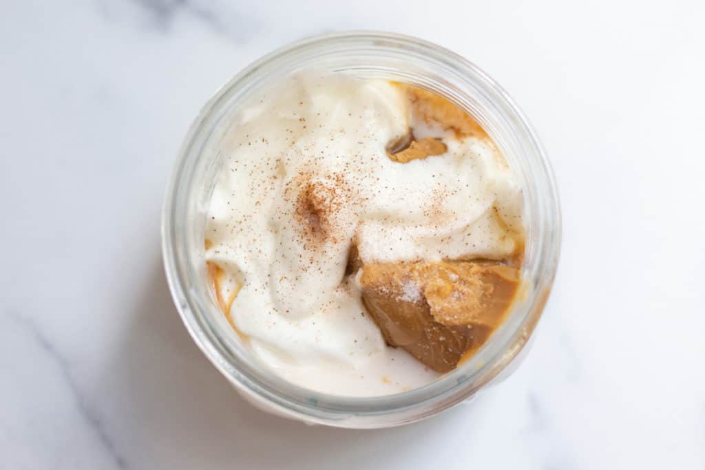 Top down view of Peanut Butter Overnight Oats ingredients in a jar.