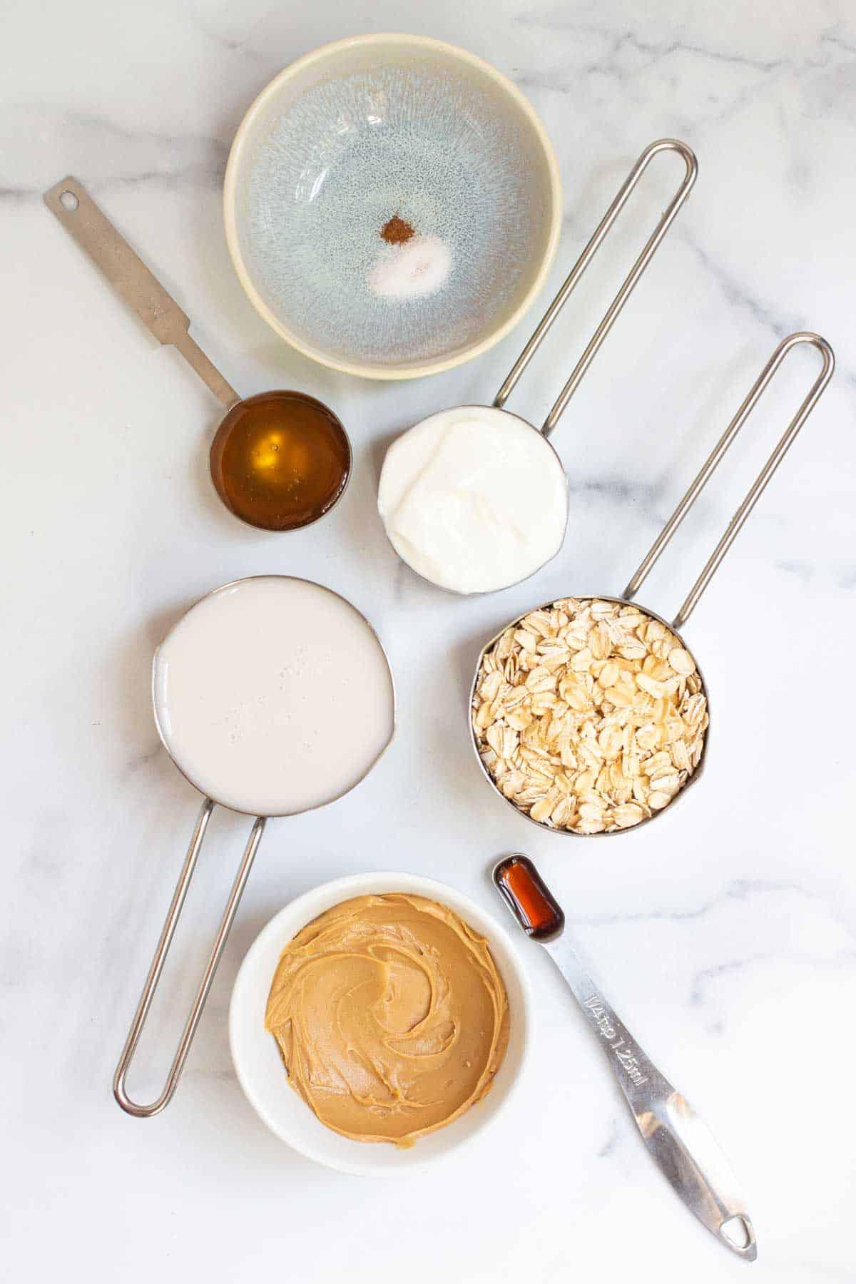 Peanut Butter Overnight Oats ingredients: oatmeals, milk, Greek yogurt, creamy peanut butter, honey, vanilla extract, salt, and cinnamon.