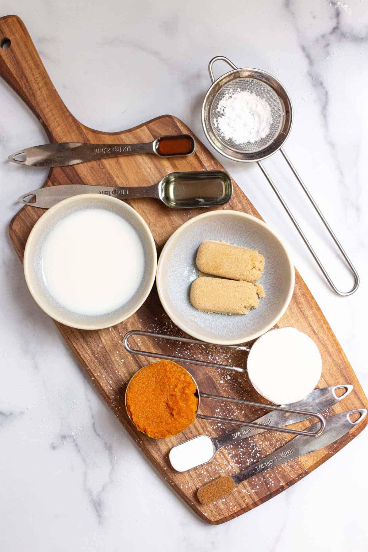 Pumpkin Mug Cake ingredients layed out: all-purpose flour, baking powder, pumpkin pie spice, salt, light brown sugar, pumpkin puree, milk, oil, pure vanilla extract, powdered sugar.