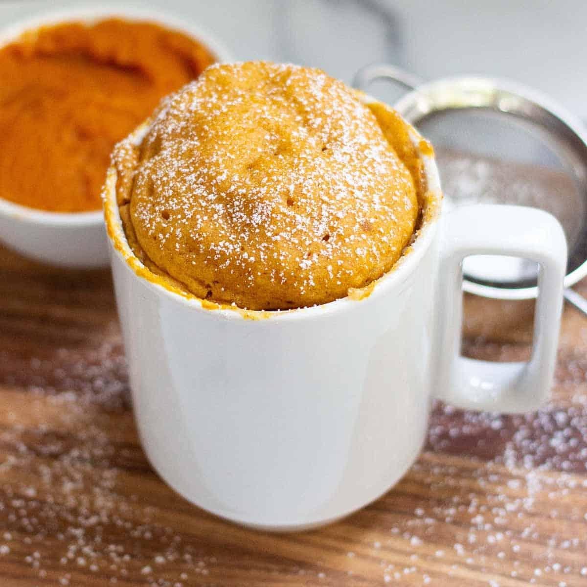 Pumpkin Mug Cake in a 12 oz mug dusted with powdered sugar.