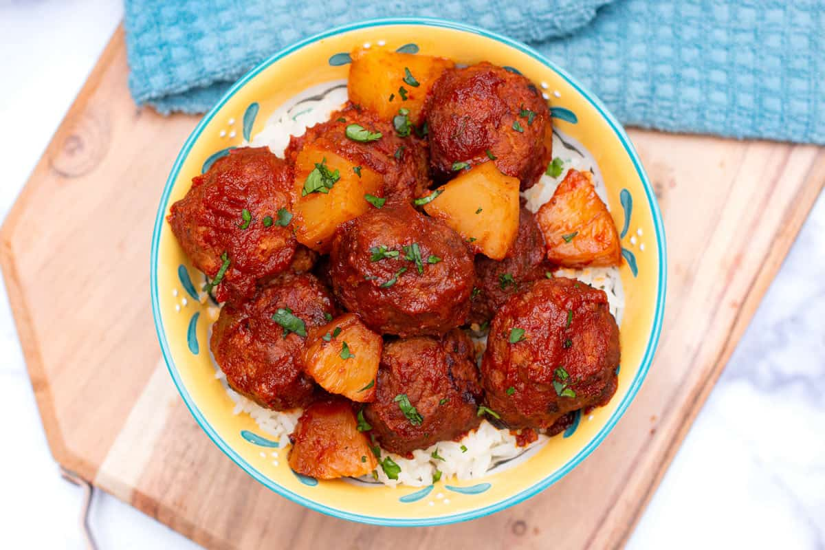 Top-down view of Hawaiian meatballs in a bowl over rice.