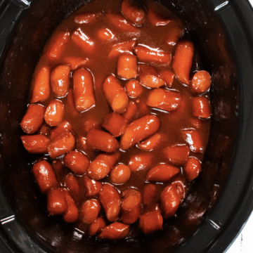 Hot dogs cut in small bite size pieces covered in BBQ sauce in a slow cooker.