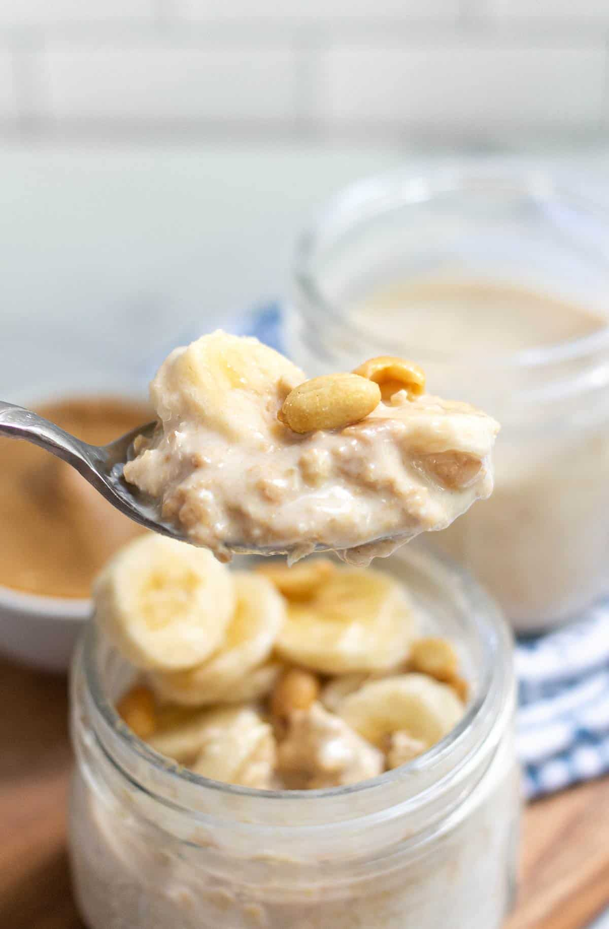 Spoonful of peanut butter overnight oats with a banana slice and peanuts on top.