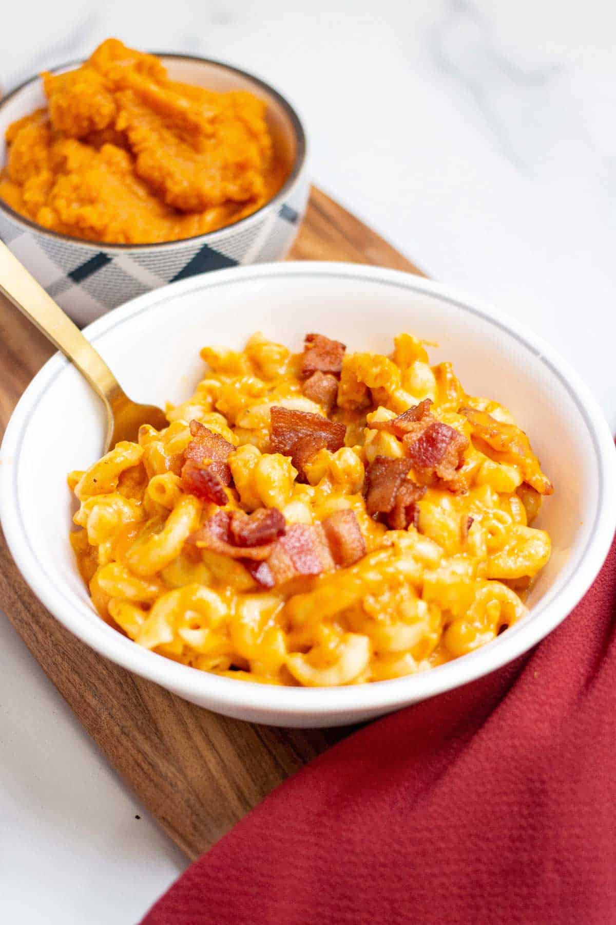 Close up of a bowl of pumpkin macaroni and cheese with cooked bacon bits scattered on top.