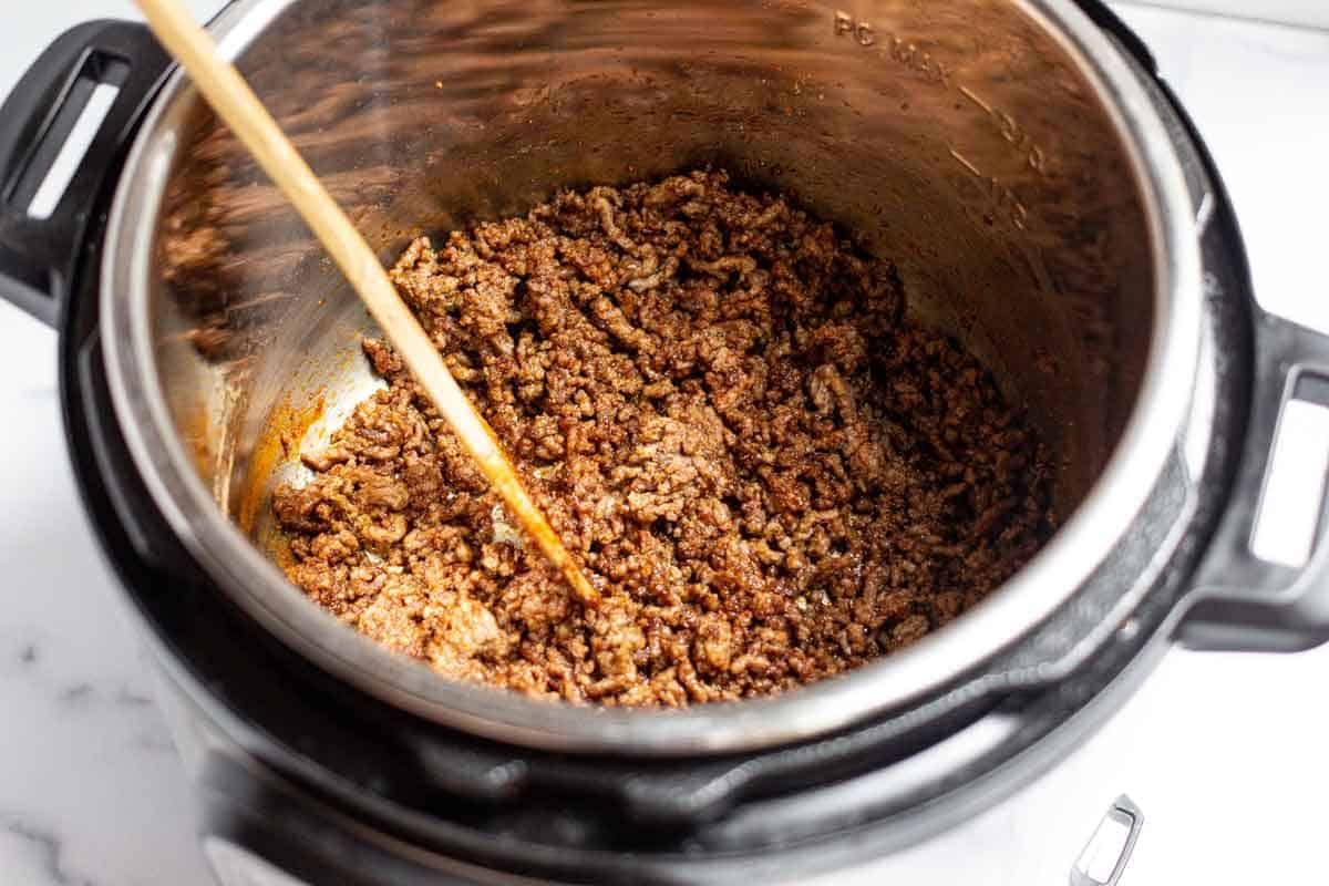 Cooked ground beef coated in seasoning in an Instant Pot liner.