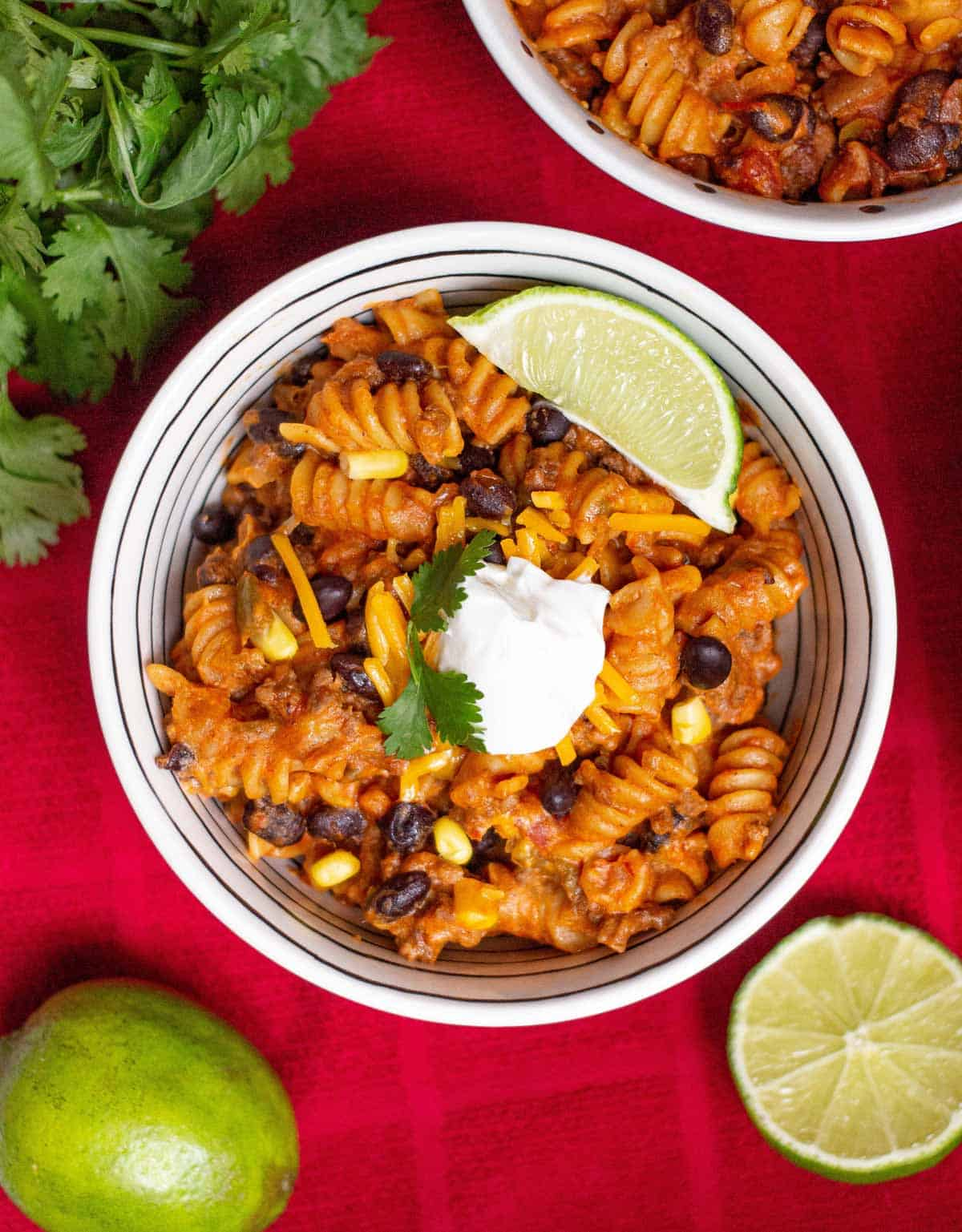 Close up of Instant Pot Taco Pasta topped with sour cream, cilantro, and a lime wedge.