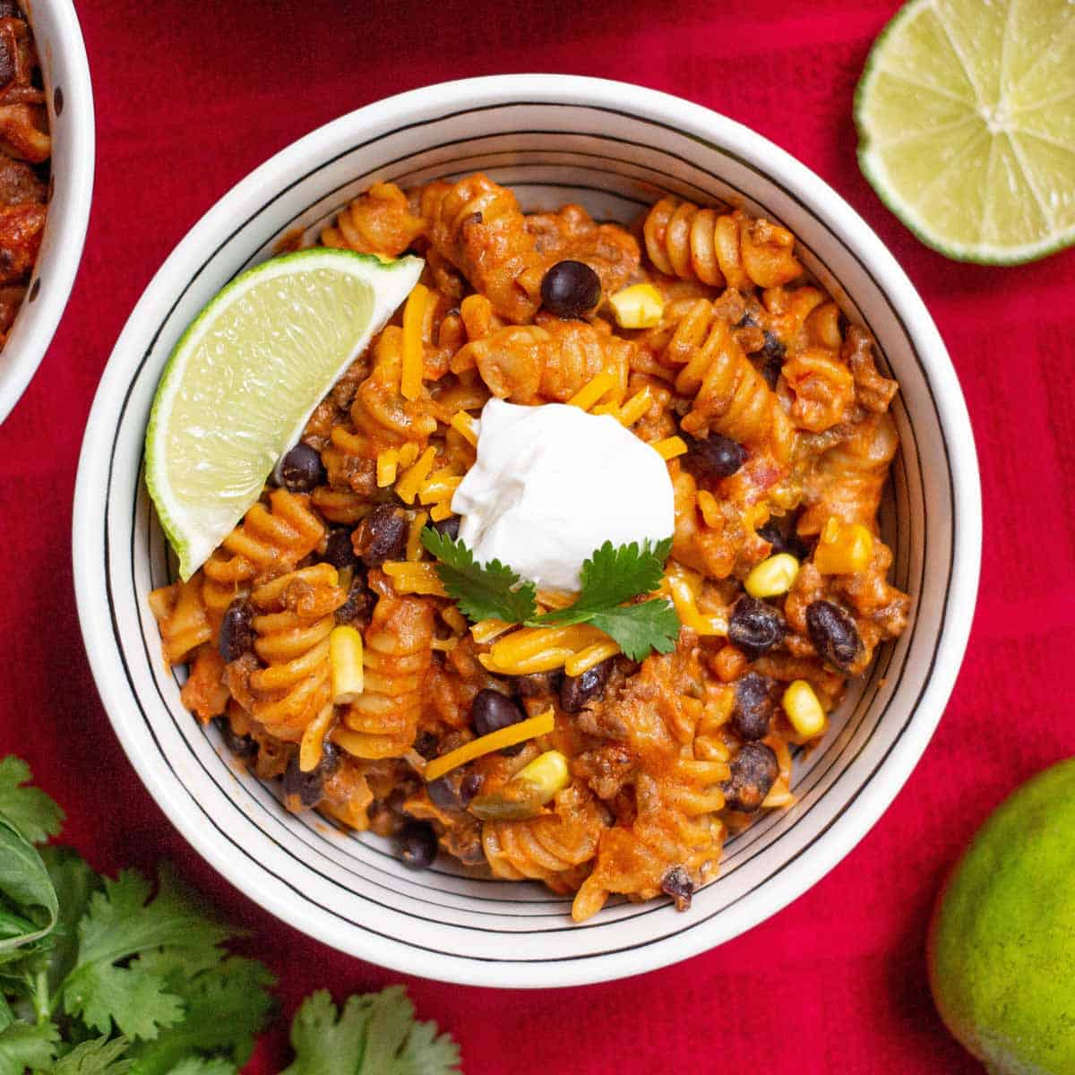 Instant Pot Beef Taco Pasta topped with a dollop of sour cream and a lime wedge.