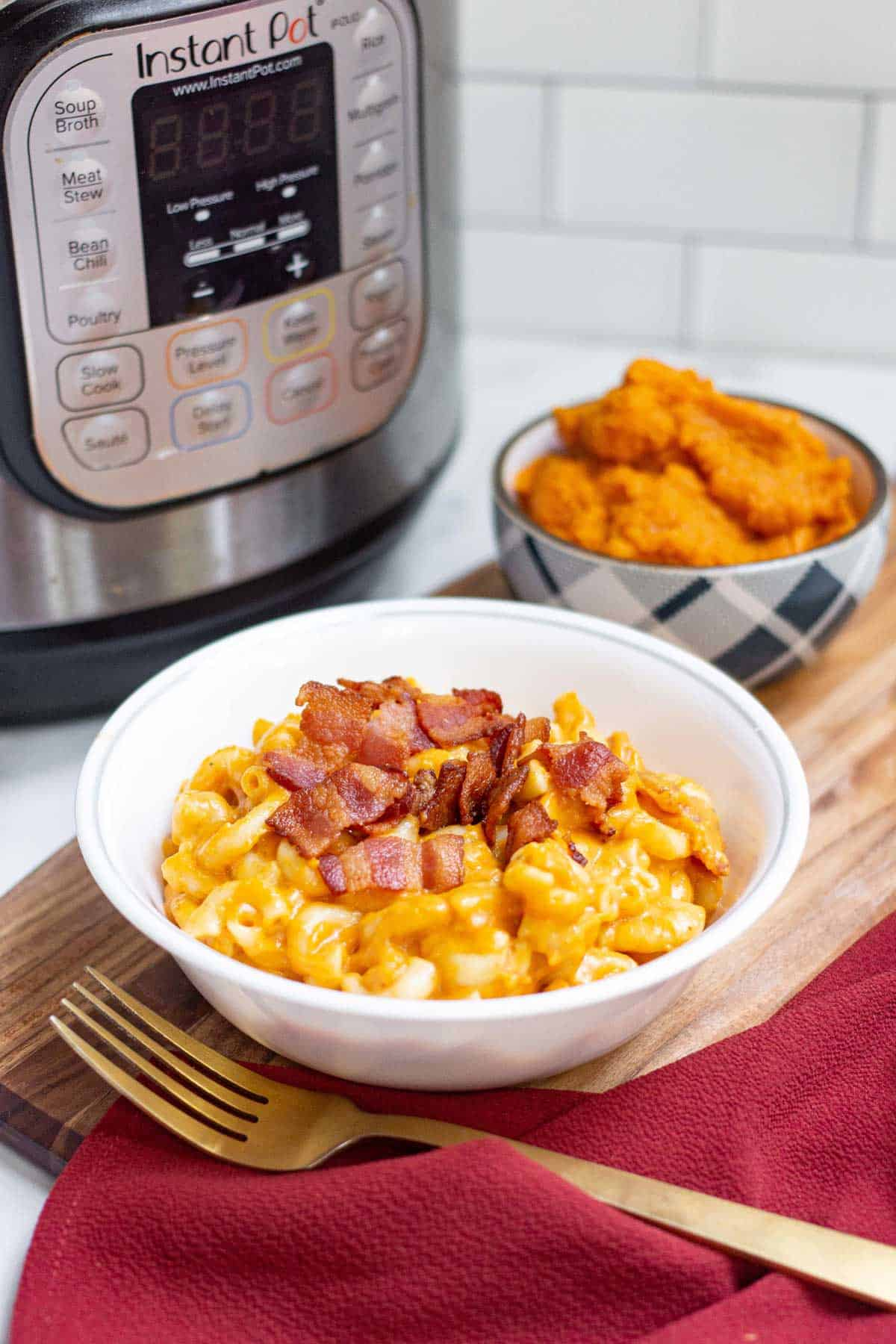 Bowl of pumpkin macaroni and cheese topped with cooked bacon bits with an Instant Pot in the background.