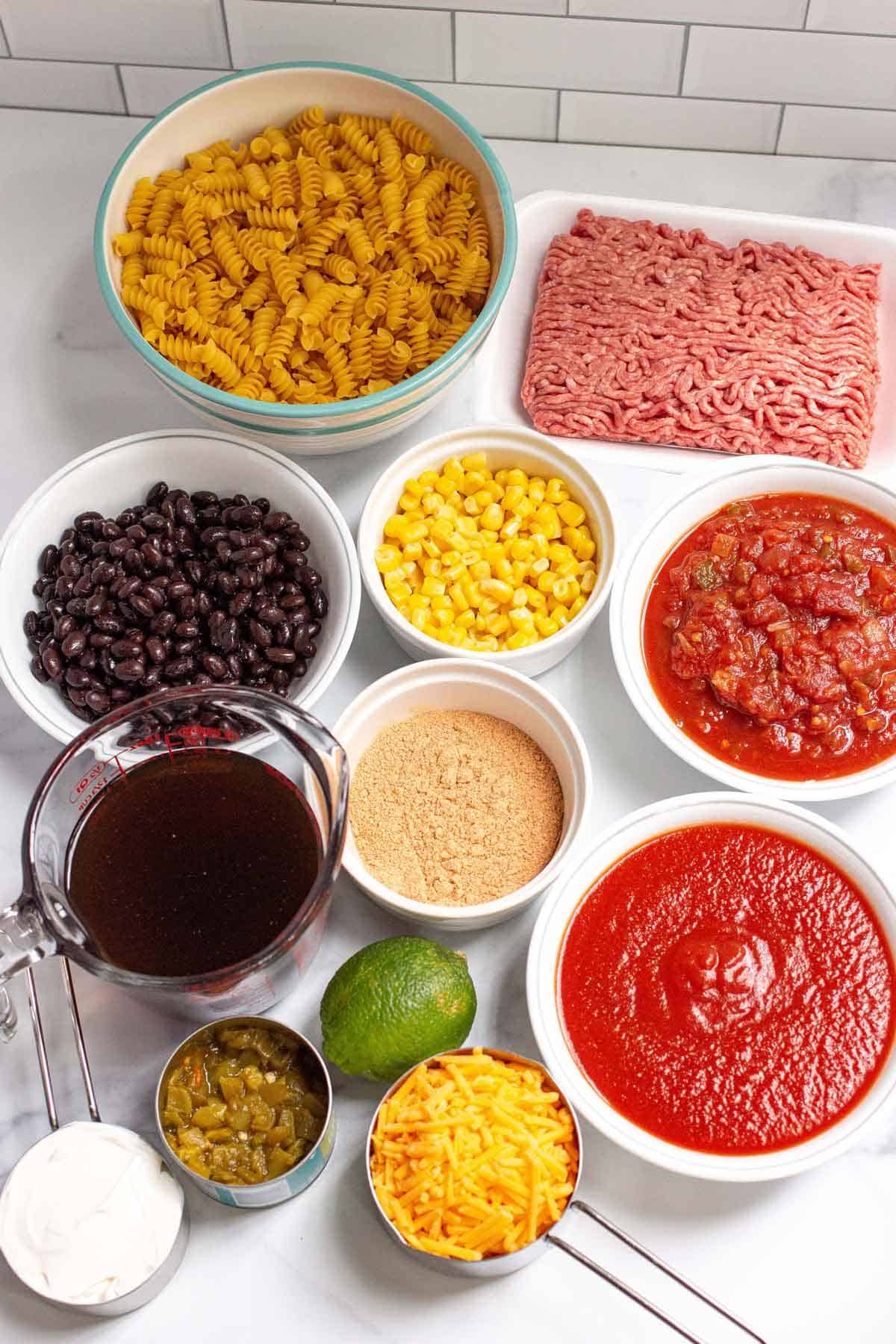 Taco pasta ingredients grouped together: ground beef, taco seasoning, black beans, sweet golden corn, diced green chiles, tomato sauce, salsa, rotini, shredded cheddar, sour cream, and lime.
