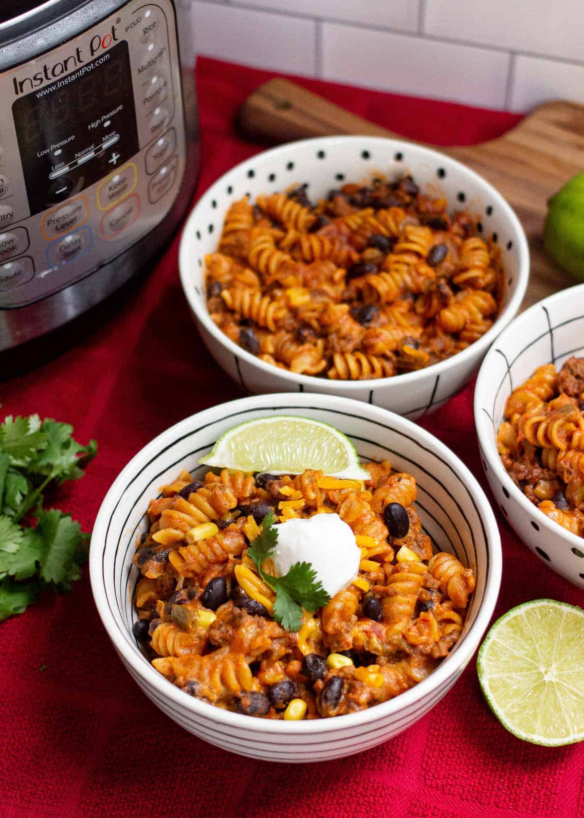 Three bowls of taco pasta topped with a dollop of sour cream, cilantro leaves, and a wedge of lime.