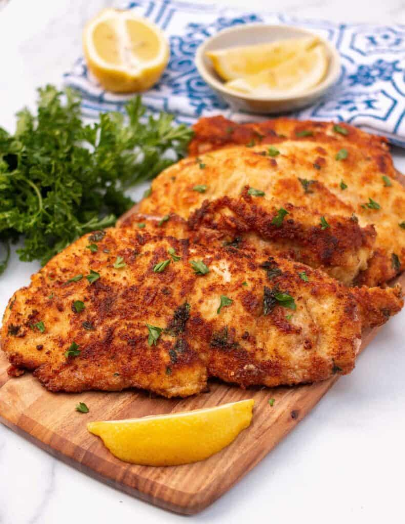 Italian chicken cutlets garnished with parsley surrounded by lemon slices.